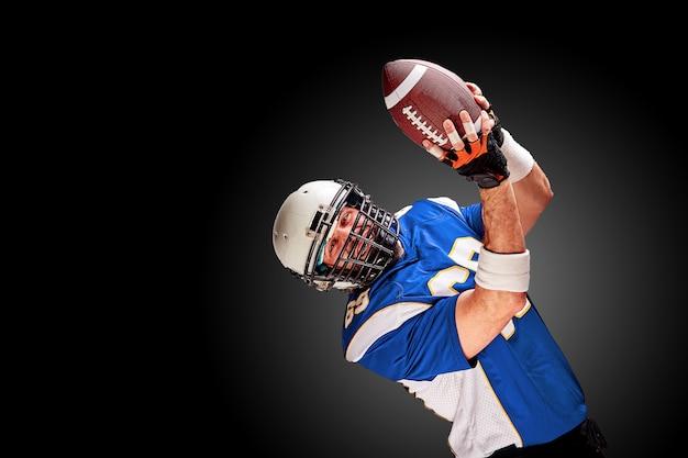 Amerikaanse voetballer in beweging met de bal Premium Foto