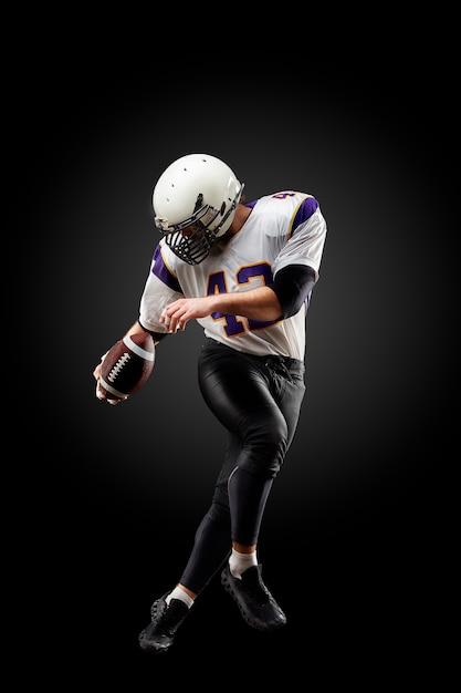 Amerikaanse voetballer in een sprong met een bal op een zwarte Premium Foto
