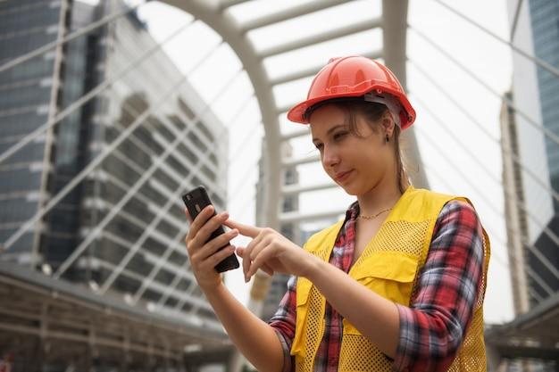 Amerikaanse vrouwelijke ingenieur die smartphone gebruiken bij plaats Premium Foto