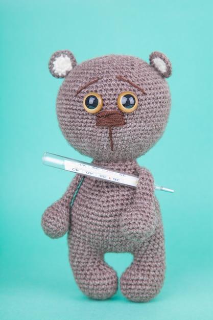 Amigurumi. diy speelgoed. gebreide bruine beerwelp met een thermometer. , preventie van kinderziekten Premium Foto