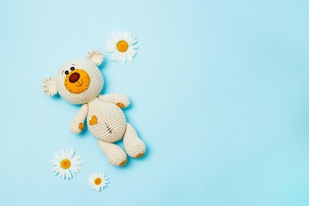 Amigurumi handgemaakte teddybeer met madeliefjes geïsoleerd op een blauwe achtergrond. baby achtergrond. ruimte kopiëren, bovenaanzicht. Premium Foto