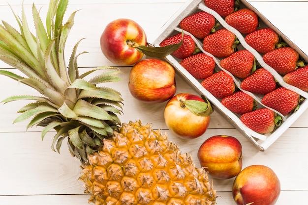 Ananas; appels en aardbeien op houten achtergrond Gratis Foto