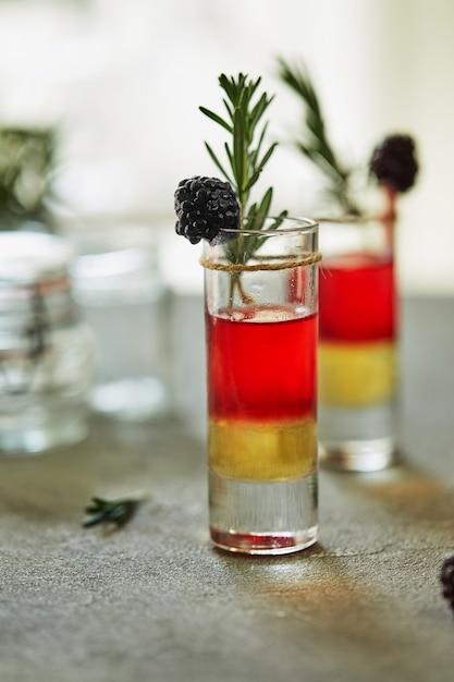 Ananas-bramencocktail in shots met een garnering van bevroren bramen en een takje rozemarijn Premium Foto
