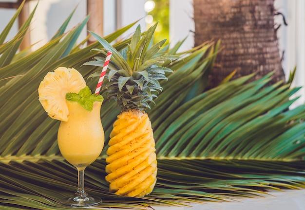Ananas en ananas smoothies tegen het oppervlak van een tak van een palmboom Premium Foto