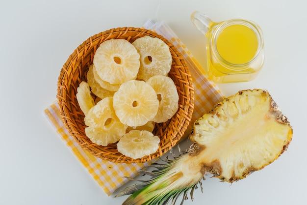 Ananas met sap en gekonfijte ringen op keukenhanddoek Gratis Foto