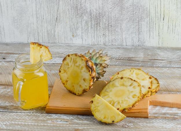 Ananas met sap en snijplank op houten en grungy oppervlak Gratis Foto