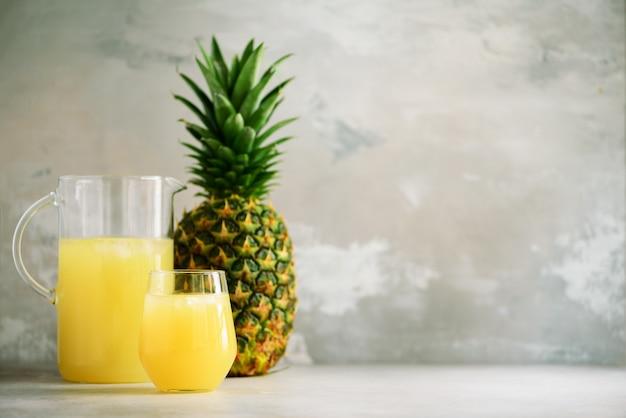 Ananassap in glaswerk en hele ananas fruit. zomer, vakantie concept. ruw, veganistisch, vegetarisch, schoon eetdieet. Premium Foto