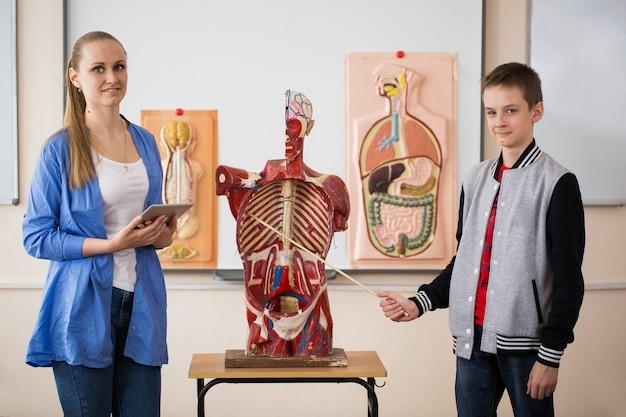 Anatomieleraar en haar leerlingen tijdens een les Premium Foto