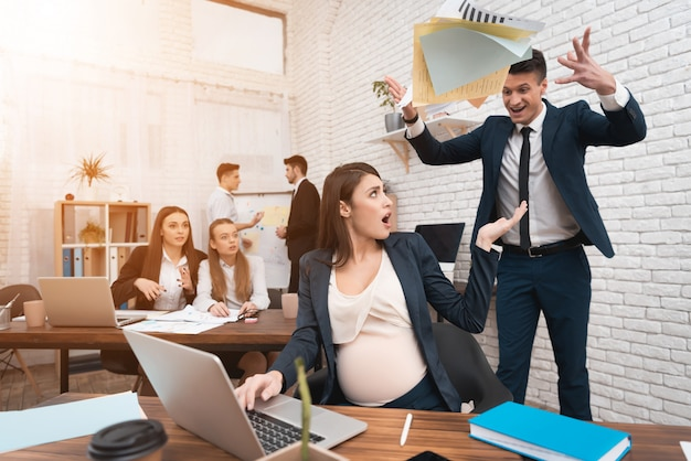 Angry irate boss yelling at pregnant employee Premium Foto