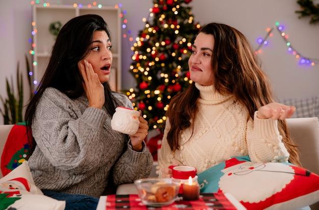 Angstig vrij jong meisje houdt beker en kijkt naar haar verwarde vriend zittend op fauteuils en genieten van kersttijd thuis Gratis Foto
