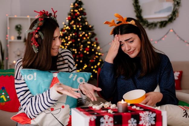 Angstig vrij jong meisje met rendieren hoofdband kijkt naar gevallen popcorn zittend op een stoel met vriend kersttijd thuis Gratis Foto