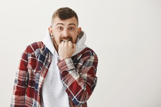 Angstige en bang hipster man bijten vuist bezorgd Gratis Foto