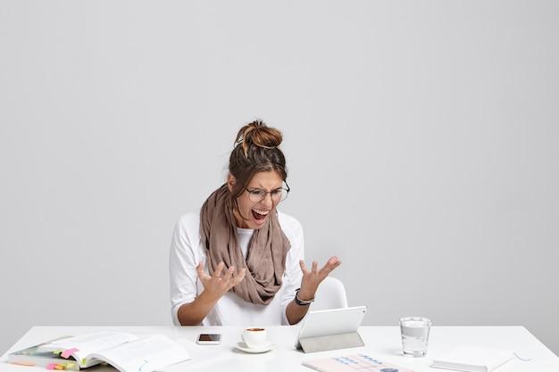 Angstige vrouw kijkt naar tablet, realiseert zich dat ze het project niet heeft opgeslagen en alles vanaf het begin moet doen Gratis Foto