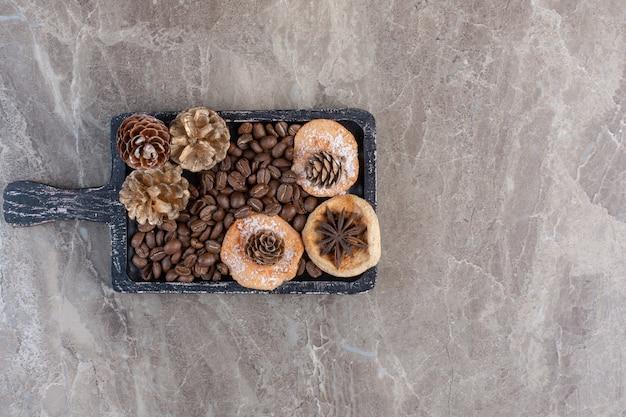 Anijs, koekjes, koffiebonen en dennenappels op marmer. Gratis Foto