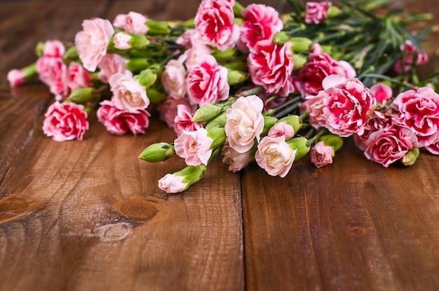 Anjer met roze en witte bloemblaadjes op een houten tafel Premium Foto