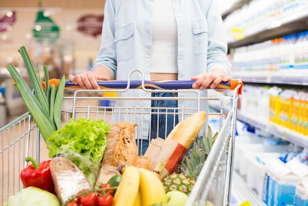 Anoniem vrouwelijk drijfboodschappenwagentje bij supermarkt Premium Foto
