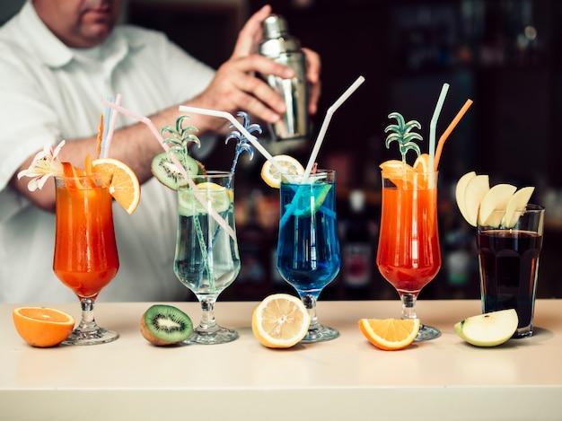 Anonieme barman die dranken in shaker mengt en heldere glazen serveert Gratis Foto