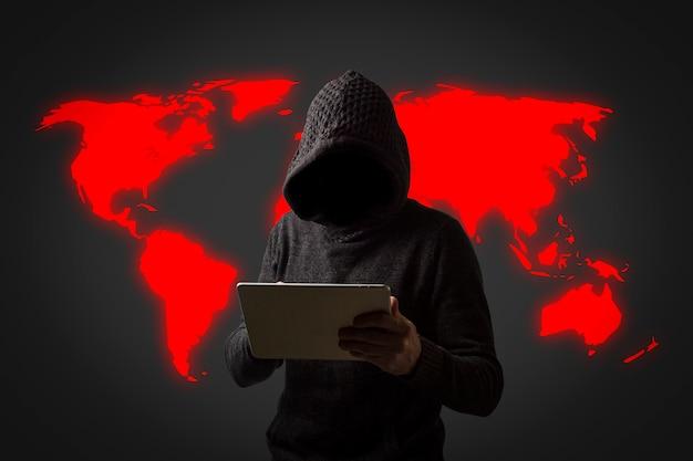 Anonieme man in een hoodie met een capuchon houdt een tablet in zijn handen op een donkere muur. concept van het hacken van gebruikersgegevens. gehackt slot, creditcard, cloud, e-mail, wachtwoorden, persoonlijke bestanden Premium Foto