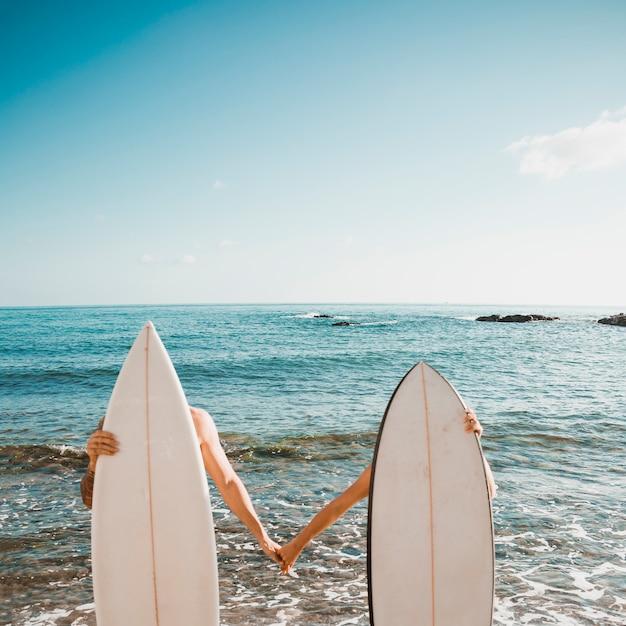 Anonieme paar achter surfplank hand in hand Gratis Foto