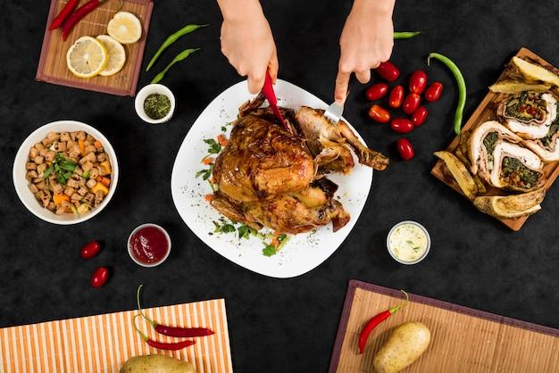 Anonieme persoon die kip voor diner snijdt Gratis Foto