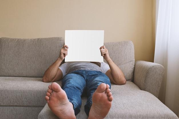 Anonieme volwassen mens die op beige bank met witte spatie ligt Premium Foto