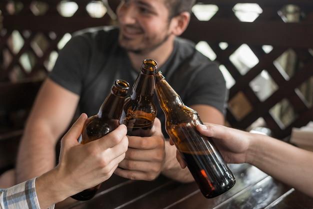 Anonieme vrienden rammelende flessen en bartafel Gratis Foto