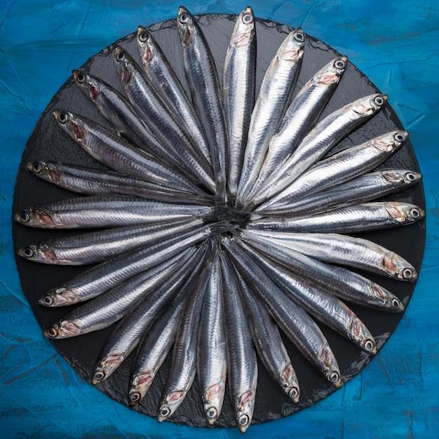 Ansjovis in de vorm van een cirkel op een zwarte steen. seafood. kleine zeevis Premium Foto