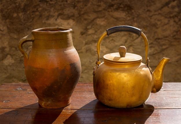 Antieke koperen theepot op retro houten tafel en klei pot Premium Foto