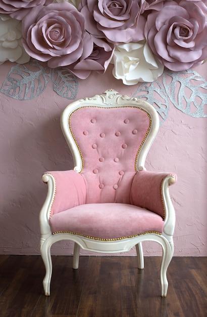 Antieke roze fauteuil met elementen van wit hout staat in de buurt van een roze muur versierd met rozen Premium Foto