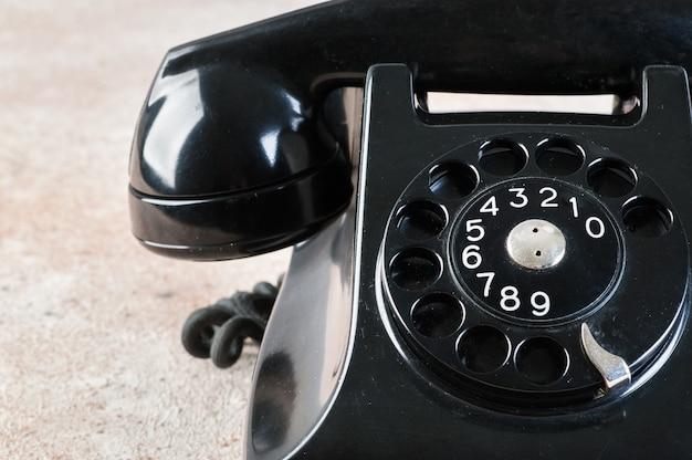 Antieke zwarte roterende telefoon op concrete achtergrond. Premium Foto
