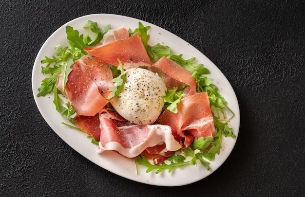 Antipasto met parmaham, mozzarella en verse rucola op de serveerschaal Premium Foto
