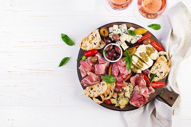 Antipastoschotel met ham, prosciutto, salami, blauwe kaas, mozzarella met pesto en olijven. bovenaanzicht, overhead Premium Foto
