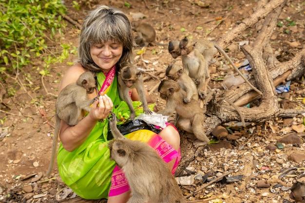 Apen omringen een gelukkige toerist die hen met fruit voedt. Premium Foto