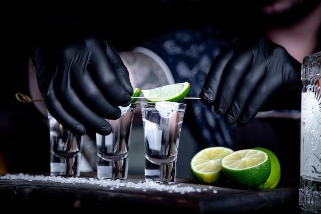 Aperitief met vrienden in de bar, drie glazen alcohol met limoen en zout voor decoratie. tequila-opnamen, selectieve aandacht Premium Foto