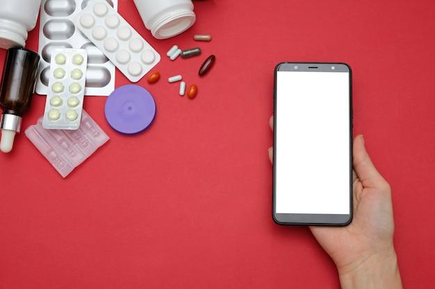 Apotheek en drogisterij online concept. geneeskundepillen en smartphone in handen op rode achtergrond Premium Foto