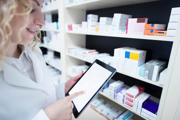 Apotheker die tablet bij de plank vol met medicijnen in de drogisterij houdt en de beschikbaarheid en specificatie van medicatie controleert Gratis Foto