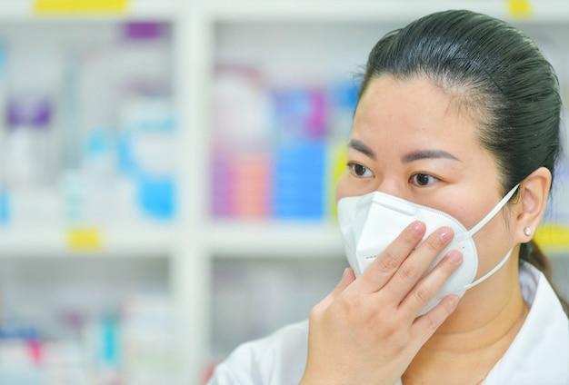Apotheker draagt n95-masker op veel medicijnplanken. coronavirus (covid-19) concept van ziekte, griepbehandeling en bescherming. kopie ruimte Premium Foto