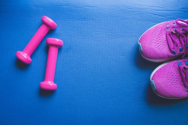 Apparatuur voor gym en thuis halter en sneakers op blauw Premium Foto