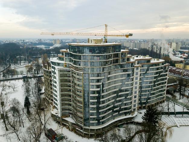 Appartement of kantoorgebouw in aanbouw, luchtfoto. toren kraan silhouet op blauwe hemel kopie ruimte achtergrond. Premium Foto