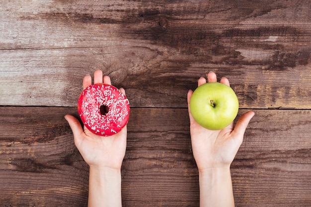 Appel en doughnut op houten achtergrond Gratis Foto