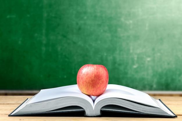 Appel in het midden van geopend boek op houten tafel met schoolbord Premium Foto