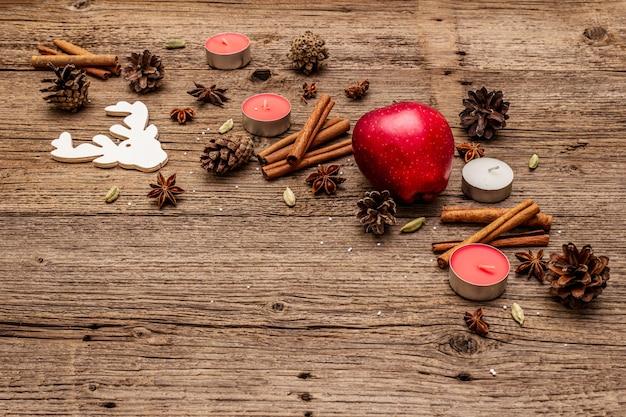 Appel, kaarsen, kruiden, herten, kegels. natuur nieuwjaar decoraties, vintage houten planken Premium Foto