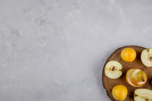 Appel, peer en perziken op een stuk hout, bovenaanzicht Gratis Foto