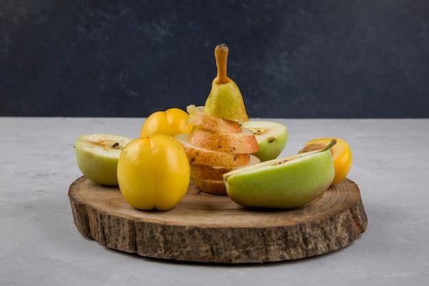 Appel, peer en perziken op een stuk hout op blauw Gratis Foto