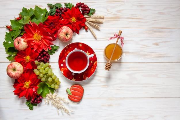 Appels, druiven, rode dahlia bloemen, rode lijsterbessen en honing met kopie ruimte Premium Foto