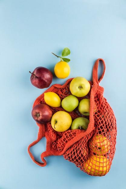 Appels en citroenen in een oranje string tas Premium Foto