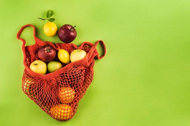 Appels en citroenen in een oranje string zak op een groene achtergrond Premium Foto