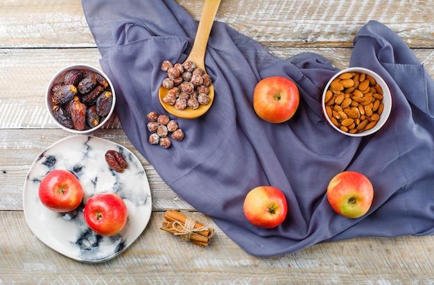 Appels in een bord met kaneelstokjes, dadels, amandelen in kommen, noten in houten lepel bovenaanzicht op houten en textiel Gratis Foto