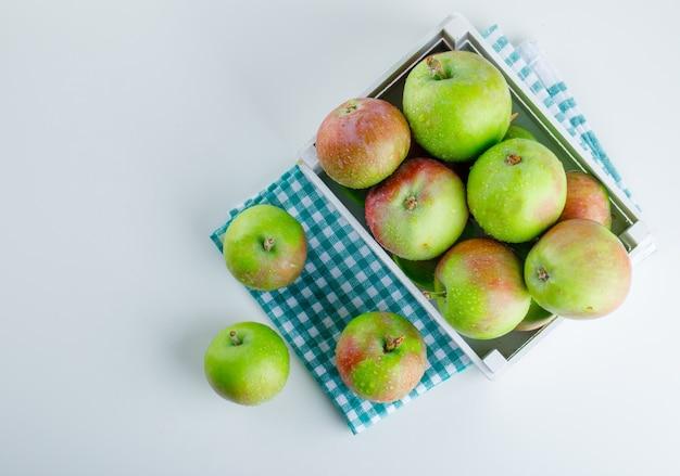 Appels in een houten kist op wit en picknickdoek. Gratis Foto