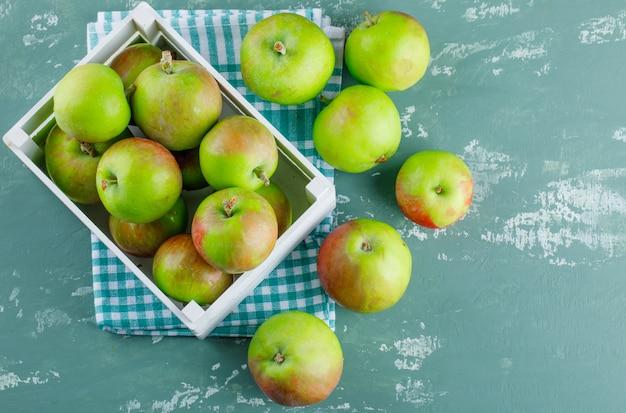 Appels in een houten kist plat leggen op gips en picknick doek achtergrond Gratis Foto